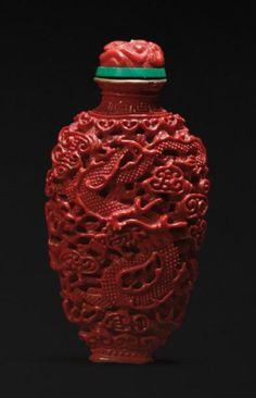 Flacon tabatière en porcelaine moulée monochrome corail imitant la laque représentant un dragon et un phénix sur fond de nuages ajourés. Le col doré. Fin XVIIIème - début XIXème siècle.. Au revers marque Jiaqing, peinte à l'or en Zhuanshu. Période Jiaqing (1796-1820) Le bouchon en corail sculpté H: 7,5 cm