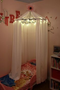 Easy bed canopy made with a hula hoop, sheer curtains, fishing line and christmas lights!