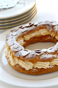 We love Paris-Brest! Did you know that it was invented in 1891 to commemorate a bicycle race between Paris and Brest? Desserts Français, French Desserts, Delicious Desserts, Yummy Food, Patisserie Paris, French Patisserie, Eclairs, Sweet Recipes, Cake Recipes