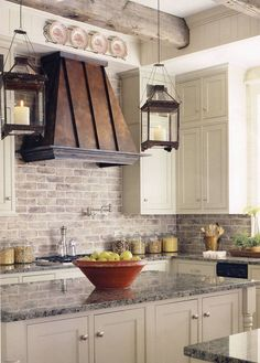 brick backsplash + metal hood + hurricane pendants + marble