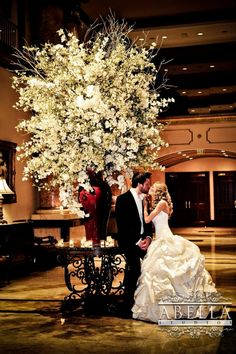 The wedding was beautiful and the couple wanted pictures taken here by this large arrangement. What a stunning photo and a stunning couple.