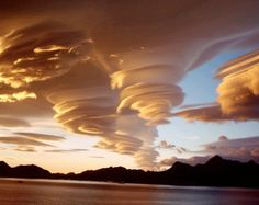 Absolutely spectacular shot of lenticular clouds over the Sandwich islands. Also known as altocumulus standing lenticularis, these are stationary, lens-shaped clouds that form at high altitudes. They are included in the middle layer cloud family because the bases of the clouds are stationed between ~ 2,000 - 7,000 meters. These clouds form when moist air is forced to flow up around mountains and large hills. The water is super cooled and condensed from air below the dew point temperature.