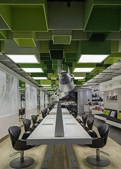 Swedish studio Sweco Architects has covered the ceiling of this hair salon in Umeå with 85 green MDF boxes.