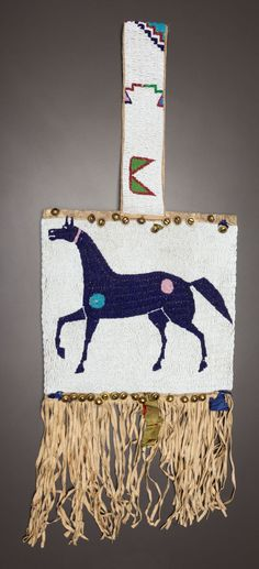 Sioux beaded and fringed hide bag with horses (side 1), c1890. Hide, sinew-sewn and beaded in lane-stitch; handle made from a legging strip, trimmed with brass hawk bells and hide fringe.