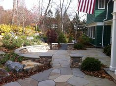 Irregular bluestone terrace with fieldstone seat wall and columns.
