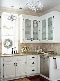 Kitchen ~ easy updates ~ replace solid doors with glass, add furniture feet, moldings, and wood applique to sink apron, handy towel bar, mini chandelier over sink...