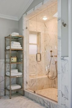 Bath Tubs Are Out - Sort Of.... Love the shower opening, the marble wainscot, petit sconce, and brass accents.