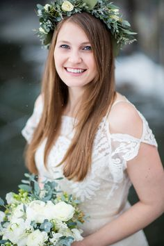 Beautiful bride in a stunning off the shoulder, short sleeve, lace boho wedding dress and eucalyptus flower crown and wedding bouquet for dreamy winter wedding at Lake Placid Lodge