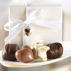 Wedding Favor - Our White 4 piece chocolate favor is tied with white ribbon and a silver heart charm. Includes a Milk Chocolate Praline Heart, Dark Chocolate Ganache Bliss, White Chocolate Raspberry Star, and Dark Chocolate Caramel Embrace.