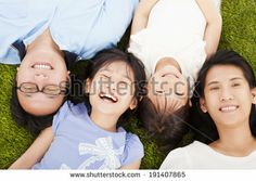 happy family lying on a meadow together by Tom Wang, via Shutterstock