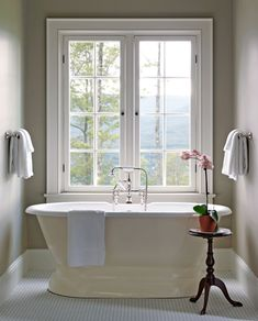 A pedestal bathtub offers scenic views of the New Hampshire forests and Mount Washington in this clean and classic master bath - Traditional Home®  Photo: Jonny Valiant and Joseph St. Pierre Design: Nancy Gould