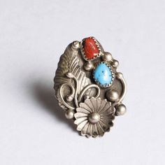 Delicately hand-crafted 1950s ring with coral and turquoise stone set into sterling silver with ornate leaf and flower details. Good condition. Ring size 8.