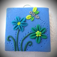 """""""Summer afternoon"""" Square polymer clay pendant, handmade with applique technique, one of a kind. Sparkly blue with a turquoise and a green flowers with yellow centers and dark green stems and a silver, yellow and green dragonfly. By Lis Shteindel."""