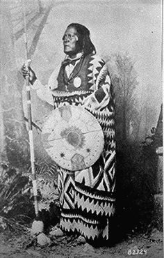 San Juan, a Mescalero Apache chief; standing,                       full-length, holding a spear and shield.