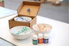 """Si StudioPendulum Painting Bowl """"Travellers"""": los bowls en blanco, se ponen dentro de la caja. Desde la tapa, cuelga un gotario lleno de pintura para cerámica, cuyo movimiento pendular pinta el interior del bowl. El gotario se mueve durante el viaje hasta que el paquete llega a su destino y se revela el diseño del bowl."""