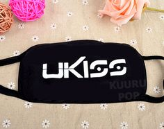 U-KISS Face Mask  These black face masks are printed with the UKISS logo in white. The cotton masks have two elastic loops that hook over your ears to comfortably hold it in place. Face masks have become a staple of Korean fashion and they're also ideal for keeping dust and germs away!