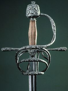 """Rapier Dated: approximately 1610-1620 Culture: French Medium: steel, copper Measurements: Overall length: 985 mm. Blade length: 963 mm; width: 203 mm. Blade width: 29 mm. Weight: 1,293 g  Inscriptions: """"COMBATRE A FOY"""" and """"ESPERANCE DE VIE"""""""
