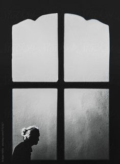 Srdjan Kirtic for Stocksy United - Silhouetted, anonymous, unrecognizable small, old lady with gray hair passing in front of the window; framed ancient, anonymous, artistic, black, black and white, capture, detail, frame, framed, glass, go, grandma, granny, gray, hair, life, minimal, motion, moving, old, old woman, on the go, one, pace, passing, past, retired, routine, senior, silhouetted, single, slow, small, street, transparent, unrecognizable, walking, window, woman