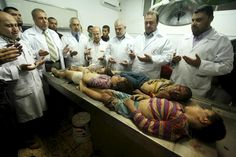 Palestinian doctors gather to pray around the bodies of four children from the al-Dallu family killed along with seven other persons when an Israeli missile struck a family home in Gaza City on 18 November.