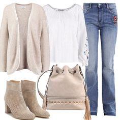 Mood vintage per questo insieme delicato, jeans bootcut con ricamo, tunica con fiorellini e bordino, avvolgente cardigan, stivali traforati e dal tacco grosso, borsa a secchiello ricamata e con frange.