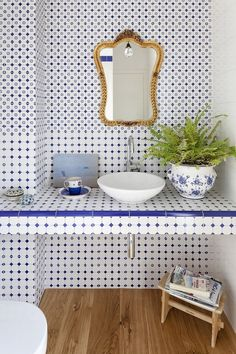Blue and white tile from floor to ceiling, with a gold French mirror and hardwood floors.
