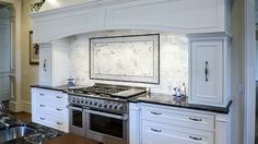 The focal point of this open kitchen is the beautiful backsplash with white statuary marble in 3 x 6 subway tile. The inside frame is the same White Statuary Marble set in a herringbone pattern, framed with basket weave and narrow Marquina pencil. Contrasting countertops are Black Forest Granite