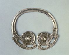 Silver bossed penannular brooch; animal heads join hoop to bossed terminals and openwork animals extend around each; no pin. England, 9th-10th century