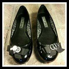 🌟HP...Coach Clara Soft Patent Leather Flats Coach poppy black patent leather flats. Soo cute with a bow and metal charms that say Coach and poppy.  There are a few little scuffs, which with patent leather is kinda easy to happen. They really aren't easily noticeable. In very good condition. SORRY NO TRADES Coach Shoes Flats & Loafers