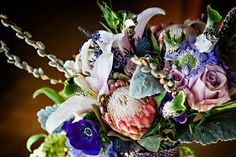 Modern cascade bouquet for Art Nouveau wedding in pinks, purples, and silver featuring pink protea, stargazer lilies, pussy willows, roses, anemone, lisianthus, scabiosa, veronica, heather, sea thistle, dusty miller. Photo by Bliss Fotography; floral design by Green Snapdragon.