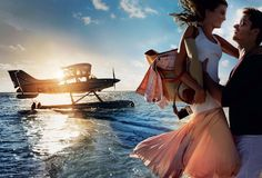 Splash Landing - The setting: Harbour Island in the Bahamas. The couple: model Cameron Russell and actor Luke Grimes (American Sniper, Fifty Shades of Grey). The mood: sensual and uncomplicated. Derek Lam 10 Crosby tank dress with pleated skirt, $240; dereklam.com. Wes Gordon pink denim jacket (in bag), $1,490; Bergdorf Goodman, NYC. Hermès tote. Pentax Q-S1 digital camera. On Grimes: Façonnable sweater. Solid & Striped pants. Oliver Peoples sunglasses.   Fashion Editor: Tonne Goodman