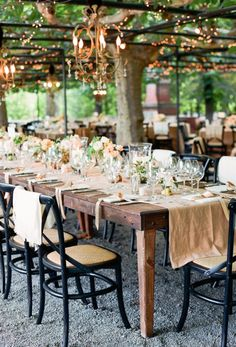 Chandeliers float above rustic wooden dining tables