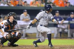 New York Yankees batter Curtis Granderson triples to center field against Baltimore Orioles relief pitcher Tommy Hunter during the ninth inn...