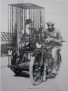 A police officer on a Harley and an old fashioned mobile holding cell, 1921.
