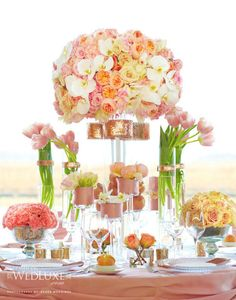 There is no shortage of prettiness in this over the top pink and peach tablescape! From the main floral centrepiece with garden and cabbage roses, orchids and peonies, to the slim vases of tulips, to the smaller floral bunches around the base, we are loving this look.