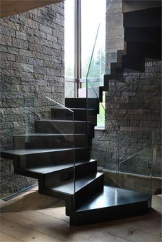 A glossy black staircase against wood, stone and glass.