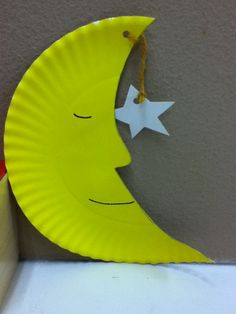 Moon and stars craft using paper plate, paint, and yarn.