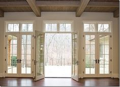 triple french doors with transom windows above. I would replace the french doors with the sliding pocket doors. Transom Windows, Floor To Ceiling Windows, Windows And Doors, Ceiling Beams, Wall Of Windows, House Windows, Living Room Double Doors, Living Room With Windows, French Doors With Screens