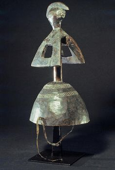 A fine Mumuye headdress Nigeria, of atypical form, a classically rendered head and stylized triangular open-worked arms rising from a cylindrical body; the whole attached to a carved hollow dance crest with incised carved geometric bands. Fine lustrous variegated surface. height 16 1/2in FOOTNOTES