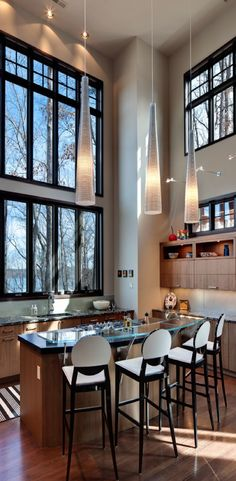 Modern decor with class and character.  I love the high ceilings, the wall of windows and those hanging lamps!