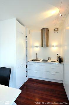 Une petite cuisine blanche moderne avec parquet foncé au sol.