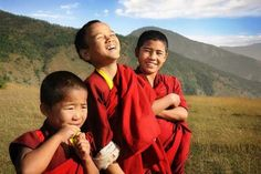 Three happy novice monks stand together high up in the mountains of Bhutan.