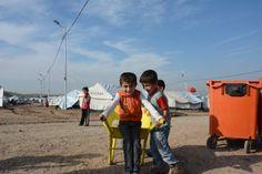 Syrische jongentjes spelen met een kruiwagen in het Gawilan vluchtelingenkamp in Irak.