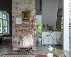 Exposed brick walls in this converted railway house, bike in kitchen, and small artwork