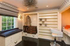 Stunning closet features a gray sea urchin pendant illuminating a built-in nook filled with stacked Louis Vuitton Monogram Luggage next to built in shoe shelves.