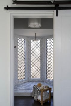 A white barn style door opens to a stunning leaded glass, oriel bay window shower illuminated by a Barbara Barry Simple Scallop Pendant features marble herringbone wall tiles and marble basketweave shower floor and fitted with an overhead, square shower head and his accented with ebony hardwood floors and a small teak shower table.