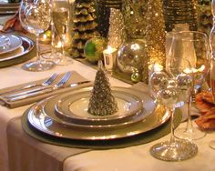 I like the idea of using a second wine glass or goblet to hold ornaments at each place...it could hold flowers, greenery, or other objects that echoed the centerpiece at an individual level. Also like the napkin/runner over the tablecloth, plus a matching napkin.