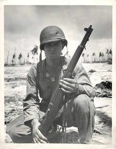 1943- U.S. soldier poses with his M1 Garand rifle on Tarawa. Note hole in helmet.