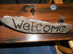 Welcome sign on driftwood sits on ground custom hanging options available. $17.00, via Etsy.