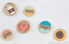 What are these cuties? Magnets! How did we make them? By lightly stamping designs onto wood discs, tracing them with a wood-burning tool, painting them, and gluing craft magnets to the back.