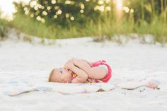 baby beach photography. a sweet 6 month old baby on a beach grabbing her toes.